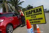 Petugas gabungan memeriksa kelengkapan surat izin keluar masuk (SIKM) yang melintas di check point penyekatan arus mudik di Gerbang Tol Karawang Barat, Jawa Barat, Jumat (7/5/2021). Pemeriksaan pengendara di akses transportasi tersebut dalam rangka pemberlakuan larangan mudik Lebaran dan mengantisipasi risiko peningkatan kasus penularan COVID-19 jelang perayaan Hari Raya Idul Fitri 1442 H. ANTARA JABAR/M Ibnu Chazar/agr