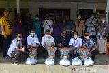 SALURKAN SEMBAKO UNTUK TUNANETRA TERDAMPAK COVID-19. Wakil Walikota Banda Aceh, Zainal Arifin (ketiga kiri) bersama Ketua Forum Komunikasi Badan Usaha Milik Negera (FKBUMN) Aceh, Ferry Heriawan (kedua kiri) bersama  penyandang Tunanetra seusai penyerahan paket sembako di Banda Aceh, Aceh, Jumat (7/5/2021). FK BUMN Aceh menyalurkan bantuan paket sembako kepada penyandang Tunanetra  yang kehilangan pekerjaan sebagai jasa pijat di sejumlah Panti Pijat  akibat pandemi COVID-19. ANTARA FOTO/Ampelsa.