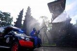Petugas kepolisian menyemprotkan disinfektan di kawasan Legian, Badung, Bali, Jumat (7/5/2021). Penyemprotan disinfektan organik dengan cairan Eco-Enzyme tersebut dilakukan di sejumlah titik di kawasan wisata Legian dan Seminyak untuk mencegah penyebaran virus COVID-19 sekaligus sebagai salah satu upaya persiapan pembukaan pariwisata Bali bagi wisatawan mancanegara. ANTARA FOTO/Fikri Yusuf/nym.