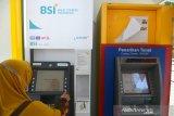 BSI PERCEPAT OPTIMALISASI LAYANAN ATM DI ACEH. Nasabah melakukan transaksi keuangan di  Anjungan Tunai Mandiri (ATM)  Bank Syariah Indonesia Tbk  di Banda Aceh, Aceh, Minggu (9/5/2021). Bank Syariat Indonesia (BSI) di Aceh terus berupaya membenahi sistem dan operasional sebanyak 450  unit ATM ex-BRIS dari total sekitar 900 unit ATM tersebar di Aceh dalam upaya percepatan dan optimalisasi layanan keuangan masyarakat menjelang Idul Fitri. ANTARA FOTO/Ampelsa.ANTARA FOTO/AMPELSA (ANTARA FOTO/AMPELSA)