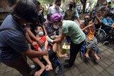 Petugas kesehatan menyuntikkan vaksin COVID-19 kepada penyandang tuna daksa di Rumah Bisabillitas, Denpasar, Bali, Minggu (9/5/2021). Pemerintah Kota Denpasar menggelar vaksinasi bagi penyandang disabilitas yang diikuti 384 orang untuk pencegahan penyebaran COVID-19 sekaligus percepatan Bali bebas COVID-19. ANTARA FOTO/Nyoman Hendra Wibowo/nym.