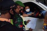 Petugas memeriksa surat keterangan bebas COVID-19 saat penyekatan dalam rangka larangan mudik di pos penyekatan exit tol Dumpil, Kabupaten Madiun, Jawa Timur, Sabtu (8/5/2021). Penyekatan yang dilakukan petugas gabungan TNI, Polri, Satpol PP, Badan Penanggulanan Bencana Daerah (BPBD) dan ormas itu dimaksudkan untuk mengantisipasi pemudik masuk wilayah Kabupaten Madiun guna mencegah penularan COVID-19, dan beberapa kendaraan terpaksa harus berputar balik karena tak bisa menunjukkan surat keterangan bebas COVID-19. Antara Jatim/Siswowidodo/zk