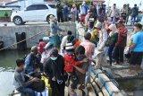 Penumpang kapal motor antre menaiki kapal saat larangan mudik di Pelabuhan Kalbut, Mangaran, Situbondo, Jawa Timur, Sabtu (8/5/2021). Pada masa larangan mudik Lebaran 2021, sejumlah warga Pulau Sapudi, Sumenep tetap mudik menggunakan kapal motor barang yang minim alat keselamatan. Antara jatim/Seno/zk