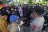 Anggota Polisi memberikan pengarahan kepada Pekerja Migran Indonesia (PMI) sebelum menjalani karantina di Islamic Center, Pamekasan, Jawa Timur, Senin (10/5/2021). Sejak pertengahan bulan Ramadan lalu hingga H-2 Idul Fitri 1442 H. Jumlah kedatangan PMI di Kabupaten Pamekasan mencapai sekitar 485 orang. Antara Jatim/Saiful Bahri/zk