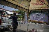 Seorang muzaki memberikan zakat berupa beras kepada petugas Pusat Zakat Umat (PZU) pada layanan pembayaran zakat tanpa turun di PP Persis, Bandung, Jawa Barat, Senin (10/5/2021). Layanan pembayaran zakat tanpa turun tersebut dilakukan untuk memberikan kemudahan bagi muzaki untuk membayar zakat, serta menghindari kontak fisik guna mencegah penyebaran COVID-19. ANTARA JABAR/Raisan Al Farisi/agr