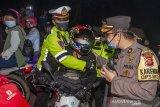 Polisi mengamankan pemudik motor yang memicu kerusuhan di jalur pantura Karawang, Jawa Barat, Senin (10/5/2021). Petugas gabungan dari TNI, Polri, Dishub dan Satpol PP memperketat penjagaan pemudik dari arah Jakarta menuju Jawa Barat dan Jawa Tengah pada H-3 jelang Hari Raya Idul Fitri 1442 H. ANTARA JABAR/M Ibnu Chazar/agr