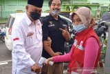 Relawan SIBAT Palang Merah Indonesia (PMI) di Kelurahan Benteng, Jawa Barat, melakukan pengecekan suhu kepada sejumlah warga dan mengingatkan masyarakat akan pentingnya menggunakan masker saat melakukan aktivitas di luar rumah. (Antara/HO/PMI/IFRC).