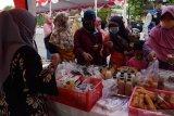 Pelaku Usaha Mikro Kecil Menengah (UMKM) melayani pembeli saat bazar makanan dan minuman Ramadhan 1442 di lapak UMKM Donopuran Kelurahan Taman, Kota Madiun, Jawa Timur, Senin (10/5/2021). Bazar UMKM yang menjual produk makanan dan minuman dengan harga antara Rp5.000 hingga Rp15.000 per kemasan dan diikuti puluhan pelaku UMKM tersebut dimaksudkan untuk membantu UMKM tetap bisa bertahan pada masa pandemi COVID-19. Antara Jatim/Siswowidodo/zk