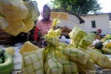 Pedagang membuat cangkang ketupat dagangannya di Pasar 17 Agustus, Pamekasan, Jawa Timur, Selasa (12/5/2021). Cangkang ketupat yang dibuat hanya untuk kebutuhan Idul Fitri 1442 H tersebut dijual Rp5.000 per ikat isi 10 cangkang. Antara Jatim/Saiful Bahri/zk