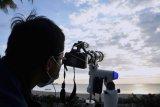 Petugas mengamati posisi hilal menggunakan teropong saat pemantauan di Pantai Jerman, Kuta, Bali, Selasa (11/5/2021). Pemantauan Hilal dilakukan di 88 titik yang tersebar di seluruh Indonesia untuk menentukan 1 Syawal 1442 Hijriah. ANTARA FOTO/Fikri Yusuf/nym.
