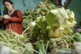 Warga menganyam daun kelapa muda untuk dijadikan Kupat (ketupat) di Blok Kupat Caringin, Bandung, Jawa Barat, Selasa (11/5/2021). Setiap tahun jelang lebaran Idul Fitri tiap warga di kampung tersebut memproduksi sedikitnya 15 ribu pesanan anyaman ketupat untuk dijual kembali di pasar tradisional dan modern dengan kisaran harga Rp500 hingga Rp1000 per anyaman ketupat atau Rp3000 hingga Rp5000 untuk anyaman ketupat yang telah berisi beras maupun ketan. ANTARA JABAR/Novrian Arbi/agr