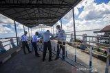 Petugas Dinas Perhubungan menutup Dermaga Feri Alalak di Banjarmasin, Kalimantan Selatan, Selasa (11/5/2021). Jalur penyeberangan kapal feri tradisional antar Kabupaten/Kota tersebut ditutup mulai tanggal 11-16 Mei 2021 guna membatasi tingginya arus keluar masuk orang dalam upaya mencegah peningkatan penyebaran COVID-19 di wilayah Kota Banjarmasin saat hari raya Idul Fitri 1442 H. Foto Antaranews Kalsel/Bayu Pratama S.