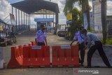 Petugas Dinas Perhubungan menutup jalur masuk ke Dermaga Feri Alalak di Banjarmasin, Kalimantan Selatan, Selasa (11/5/2021). Jalur penyeberangan kapal feri tradisional antar Kabupaten/Kota tersebut ditutup mulai tanggal 11-16 Mei 2021 guna membatasi tingginya arus keluar masuk orang dalam upaya mencegah peningkatan penyebaran COVID-19 di wilayah Kota Banjarmasin saat hari raya Idul Fitri 1442 H. Foto Antaranews Kalsel/Bayu Pratama S.