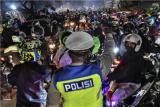 Petugas Kepolisian menghalau pemudik motor yang melawan arah untuk menghindari posko penyekatan mudik di Kedungwaringin, Kabupaten Bekasi, Jawa Barat, Minggu (9/5/2021). ANTARA FOTO/ Fakhri Hermansyah/hp.