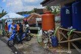 Warga membeli air asin tanjung di Kampung Cukang, Kawalu, Kota Tasikmalaya, Jawa Barat, Selasa (11/5/2021). Menjelang Hari Raya Idul Fitri sejumlah warga berburu air tanjung untuk bahan olahan ketupat lebaran dan dalam sehari pengelola bisa menjual air 500 liter air dari enam sumber mata air dikawasan tersebut. ANTARA JABAR/Adeng Bustomi/agr