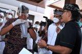 Petugas mendemonstrasikan cara pengambilan sampel nafas untuk dites menggunakan alat GeNose C19 saat peluncuran layanan GeNose C19 di objek wisata kawasan luar Pura Uluwatu, Badung, Bali, Selasa (11/5/2021). Layanan tes COVID-19 metode GeNose C19 secara gratis kepada wisatawan tersebut diharapkan dapat menjadi percontohan penerapan GeNose C19 di objek wisata guna meningkatkan kepercayaan wisatawan untuk berwisata di tengah pandemi. ANTARA FOTO/Fikri Yusuf/nym.