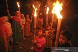 Sejumlah anak mengikuti pawai obor di Komplek Grand Cinunuk Indah, Kabupaten Bandung, Jawa Barat, Rabu (12/5/2021). Pawai obor yang diselenggarakan oleh pengurus DKM Masjid setempat tersebut ditujukan untuk menyambut Idul Fitri 1442 H yang ditetapkan oleh pemerintah pada Kamis (13/5/2021). ANTARA JABAR/Raisan Al Farisi/agr