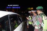 Petugas memeriksa identitas pengendara mobil berplat nomor luar daerah saat penyekatan dalam rangka larangan mudik di Kota Madiun, Jawa Timur, Selasa (11/5/2021) malam. Penyekatan yang dilakukan petugas gabungan TNI, Polri, Satpol PP, Badan Penanggulanan Bencana Daerah (BPBD) dan petugas kesehatan itu dimaksudkan untuk mengantisipasi pemudik masuk wilayah Kota Madiun guna mencegah penularan COVID-19. Antara Jatim/Siswowidodo/zk
