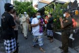 Pecalang dan petugas keamanan lainnya memberi salam kepada umat Islam seusai beribadah Shalat Idulfitri 1442 H di Mushola Silaturrahmi, Denpasar, Bali, Kamis (13/5/2021). Salat Idul Fitri di tempat tersebut melibatkan pecalang untuk menjaga keamanan dan kenyamanan umat Islam saat menjalankan ibadah. ANTARA FOTO/Nyoman Hendra Wibowo/nym.