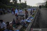 Warga menggelar alas salat untuk melaksanakan Salat Idul Fitri di ruas Jalan Tol Cileunyi-Sumedang-Dawuan (Cisumdawu) di Pamulihan, Kabupaten Sumedang, Jawa Barat, Kamis (13/5/2021). Pemerintah menetapkan 1 Syawal 1442 H pada Kamis (13/5/2021). ANTARA JABAR/Raisan Al Farisi/agr