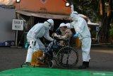 Tenaga kesehatan membantu seorang pasien COVID-19 usai pelaksanaan shalat Idul Fitri di halaman Rumah Sakit Lapangan Indrapura (RSLI) di Surabaya, Jawa Timur, Kamis (13/5/2021). Pelaksanaan shalat Idul Fitri di RS Lapangan Indrapura tersebut diikuti sekitar 30 pasien dari Pekerja Migran Indonesia (PMI) dan puluhan tenaga kesehatan. Antara Jatim/Moch Asim/zk.