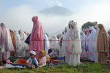 Umat muslim melaksanakan shalat Idul Fitri 1442 Hijriah di lapangan Gunung Labu dengan latar belakang Gunung Kerinci, Kayu Aro Barat, Kerinci, Jambi, Kamis (13/5/2021). Meski Pemerintah Desa setempat telah menyampaikan imbauan supaya mengikuti protokol kesehatan, sebagian warga masih terpantau enggan mengenakan masker. ANTARA FOTO/Wahdi Septiawan/hp.