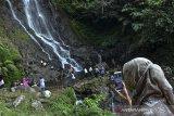 Pengunjung berkomunikasi secara daring saat mengunjungi wisata Curug Tujuh Cibolang, Kampung Sandingtaman, Kabupaten Ciamis, Jawa Barat, Jumat (14/5/2021). Wisatawan memanfaatkan libur lebaran dengan berwisata bersama keluarga di kawasan wisata alam yang dikelola Perhutani Kesatuan Pemangkuan Hutan (KPH)Ciamis. ANTARA JABAR/Adeng Bustomi/agr