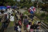 Warga berjalan untuk melaksanakan tradisi ziarah di Tempat Pemakan Umum (TPU) Sirnaraga, Bandung, Jawa Barat, Jumat (14/5/2021). Masyarakat Kota Bandung tetap melaksanakan tradisi ziarah kubur pada H+2 Idul Fitri 1442 Hijriah walau adanya imbauan pelarangan hingga penutupan TPU Sirnaraga oleh Satgas COVID-19 Bandung hingga 16 Mei 2021 guna mengantisipasi kerumunan. ANTARA JABAR/Novrian Arbi/agr