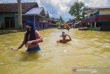 Sejumlah warga menerobos banjir yang merendam permukiman di Jalan Biduri, Kecamatan Satui, Kabupaten Tanah Bumbu , Kalimantan Selatan, Sabtu (15/5/2021). BPBD Kabupaten Tanah Bumbu mencatat sebanyak 2.126 unit rumah di Kecamatan Satui tersebut terendam banjir setinggi 50 cm hingga dua meter akibat tingginya intensitas curah hujan yang mengakibatkan meluapnya Sungai Satui. Foto Antaranews Kalsel/Bayu Pratama S.