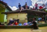 Sejumlah relawan mendistribusikan bantuan makanan kepada warga yang terdampak banjir di Jalan Biduri, Kecamatan Satui, Kabupaten Tanah Bumbu , Kalimantan Selatan, Sabtu (15/5/2021). BPBD Kabupaten Tanah Bumbu mencatat sebanyak 2.126 unit rumah di Kecamatan Satui tersebut terendam banjir setinggi 50 cm hingga dua meter akibat tingginya intensitas curah hujan yang mengakibatkan meluapnya Sungai Satui. Foto Antaranews Kalsel/Bayu Pratama S.