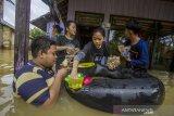 Sejumlah warga menyantap makanan saat banjir yang merendam permukiman di Jalan Antasari, Kecamatan Satui, Kabupaten Tanah Bumbu, Kalimantan Selatan, Sabtu (15/5/2021). BPBD Kabupaten Tanah Bumbu mencatat sebanyak 2.126 unit rumah di Kecamatan Satui tersebut terendam banjir setinggi 50 cm hingga dua meter akibat tingginya intensitas curah hujan yang mengakibatkan meluapnya Sungai Satui. Foto Antaranews Kalsel/Bayu Pratama S.