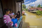 Warga bertahan di rumahnya saat banjir merendam permukiman di Jalan Biduri, Kecamatan Satui, Kabupaten Tanah Bumbu, Kalimantan Selatan, Sabtu (15/5/2021). BPBD Kabupaten Tanah Bumbu mencatat sebanyak 2.126 unit rumah di Kecamatan Satui tersebut terendam banjir setinggi 50 cm hingga dua meter akibat tingginya intensitas curah hujan yang mengakibatkan meluapnya Sungai Satui. Foto Antaranews Kalsel/Bayu Pratama S.