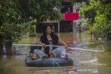 Warga menggunakan ban karet melintasi banjir yang merendam permukiman di Jalan Antasari, Kecamatan Satui, Kabupaten Tanah Bumbu, Kalimantan Selatan, Sabtu (15/5/2021). BPBD Kabupaten Tanah Bumbu mencatat sebanyak 2.126 unit rumah di Kecamatan Satui tersebut terendam banjir setinggi 50 cm hingga dua meter akibat tingginya intensitas curah hujan yang mengakibatkan meluapnya Sungai Satui. Foto Antaranews Kalsel/Bayu Pratama S.
