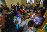 Seorang petugas mendata warga yang mengungsi di posko pengungsian korban banjir di Gedung Majelis Ta'lim Desa Sungai Danau, Kabupaten Tanah Bumbu, Kalimantan Selatan, Sabtu (15/5/2021). BPBD Kabupaten Tanah Bumbu pada Jumat (14/5/2021) mencatat sebanyak 5.308 jiwa terdampak banjir dan 207 jiwa mengungsi akibat banjir yang melanda enam Desa di Kabupaten Tanah Bumbu. ANTARA FOTO/Bayu Pratama S/nym