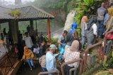 Pengunjung antre untuk menikmati panorama Air Terjun Telun Berasap setinggi 50 meter, di Gunung Tujuh, Kerinci, Jambi, Jumat (14/5/2021). Sejumlah tempat wisata alam di daerah itu mulai ramai dikunjungi warga yang memanfaatkan libur Idul Fitri meski di tengah ancaman pandemi COVID-19. ANTARA FOTO/Wahdi Septiawan/hp.