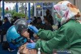 Petugas mengambil sampel lendir hidung untuk pemeriksaan tes cepat (rapid test) Antigen COVID-19 pemudik secara gratis di Unit Pelaksana Pengujian Kendaraan Bermotor (UPPKB) Balonggandu, Karawang, Jawa Barat, Minggu (16/5/2021). Kegiatan tersebut untuk mencegah penyebaran dan peningkatan kasus COVID-19 setelah Lebaran. ANTARA JABAR/M Ibnu Chazar/agr