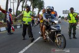 Petugas gabungan menghalau pemudik sepeda motor saat penyekatan arus balik mudik di Desa Balonggandu, Jatisari, Karawang, Jawa Barat, Minggu (16/5/2021). Penyekatan transportasi tersebut mengarahkan pemudik motor untuk melakukan rapid test swab antigen guna meminimalisir kasus penyebaran COVID-19 setelah Lebaran. ANTARA JABAR/M Ibnu Chazar/agr