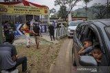 Sejumlah pemudik menunggu keluarganya yang sedang menjalani tes usap cepat di posko penyekatan jalur Lingkar Nagreg, Kabupaten Bandung, Jawa Barat, Senin (17/5/2021). Pada H+4 Hari Raya Idul Fitri 1442 H, Polresta Bandung menyediakan layanan tes usap cepat secara acak bagi pemudik, serta arus balik di Jalur Nagreg terpantau ramai lancar. ANTARA JABAR/Raisan Al Farisi/agr