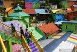 Wisatawan berekreasi di Kampung Warna-warni, Jodipan, Malang, Jawa Timur, Senin (17/5/2021). Pengelola kampung wisata tersebut mencatat, sejak diberlakukannya penyekatan arus lalulintas terkait larangan mudik lebaran jumlah wisatawan yang berkunjung menurun dari sekitar 200 orang menjadi 80 orang per hari. Antara Jatim/Ari Bowo Sucipto/zk