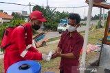 Relawan SIBAT PMI memberikan cairan hand sanitizer sekaligus memberikan edukasi pentingnya implementasi protokol kesehatan dan Perilaku Hidup Bersih dan Sehat (PHBS) kepada seorang pedagang.(Foto Antara/HO/PMI/IFRC).
