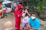 Relawan SIBAT PMI membagikan masker sambil memberi informasi tentang  Perilaku Hidup Bersih dan Sehat (PHBS) yang menjadi kewajiban dalam kehidupan sehari-hari kepada warga. (Foto Antara/HO/PMI/IFRC).