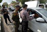 Polisi memeriksa surat keterangan sehat bebas COVID-19 pengemudi mobil saat penyekatan arus balik Lebaran dalam Operasi Ketupat Agung 2021 di Badung, Bali, Senin (17/5/2021). Direktorat Lalu Lintas Polda Bali merilis data kumulatif kegiatan penyekatan larangan mudik selama tanggal 6 hingga 16 Mei 2021 di kabupaten/kota se-Bali yakni sebanyak 396 kendaraan diputar balik arah dan penindakan pelanggaran travel gelap berjumlah 16 kendaraan. ANTARA FOTO/Nyoman Hendra Wibowo/nym.