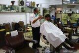 Pemangkas rambut Sukadi, memotong rambut seorang pelanggan di gerai pangkas rambut Sahabat di komplek pertokoan Kayutangan Heritage, Malang, Jawa Timur, Senin (17/5/2021). Usaha pangkas rambut yang didirikan sejak tahun 1965 tersebut kini dikelola generasi kedua dengan dua orang pekerja yang sudah berusia rata-rata 70 tahun. Antara Jatim/Ari Bowo Sucipto/zk