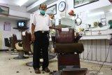 Pemangkas rambut Sukadi, berpose di gerai pangkas rambut Sahabat di komplek pertokoan Kayutangan Heritage, Malang, Jawa Timur, Senin (17/5/2021). Usaha pangkas rambut yang didirikan sejak tahun 1965 tersebut kini dikelola generasi kedua dengan dua orang pekerja yang berusia rata-rata 70 tahun. Antara Jatim/Ari Bowo Sucipto/zk
