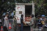 Petugas memeriksa muatan dari sebuah truk di posko penyekatan arus balik di perbatasan Kabupaten Bandung dan Kota Bandung di Cibiru, Bandung, Jawa Barat, Senin (17/5/2021). Posko penyekatan Cibiru telah memutarbalikan sebanyak 683 kendaraan roda dua dan 73 roda dua sejak diberlakukannya larangan mudik pada 6 Mei 2021. ANTARA JABAR/Raisan Al Farisi/agr