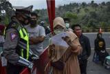 Petugas memberikan hasil pemeriksaan tes cepat (rapid test) Antigen COVID-19 kepada pemudik di Jalur Selatan Pos penyekatan leter U Gentong, Kabupaten Tasikmalaya, Jawa Barat, Minggu (16/5/2021). Pemerintah menggelar random atau acak testing COVID-19 secara gratis bagi pemudik yang melintas di Jalur Selatan, Jawa, menuju Bandung dan Jakarta untuk mengantisipasi lonjakan kasus COVID-19 pasca Lebaran. ANTARA FOTO/Adeng Bustomi/hp.