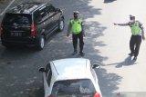 Anggota polisi mengarahkan pengendara mobil berplat nomor luar daerah untuk melakukan swab antigen di Kota Kediri, Jawa Timur, Selasa (18/5/2021). Satlantas Polres Kediri Kota melakukan pengetatan pascapeniadaan mudik dengan menggelar swab antigen di jalur perbatasan kota. Antara Jatim/Prasetia Fauzani/zk