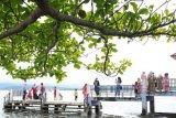 Pengunjung berfoto di tepi Danau Kerinci, Kerinci, Jambi, Senin (17/5/2021). Danau Kerinci yang sempat ditutup pada 15-16 Mei 2021 guna mengantisipasi membludaknya kunjungan wisatawan yang memanfaatkan libur Idul Fitri tersebut mulai dibuka kembali pada Senin (17/5). ANTARA FOTO/Wahdi Septiawan/wsj.