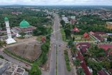 Foto udara suasana kendaraan saat melintasi Jalan Lintas Tengah Sumatera di Pasir Putih, Bungo, Jambi, Selasa (18/5/2021). Lalu lintas kendaraan di jalan penghubung Jambi dengan Sumatera Barat tersebut terpantau normal, sementara sejumlah pemudik terpantau melintas bebas di tengah tidak maksimalnya penyekatan oleh petugas. ANTARA FOTO/Wahdi Septiawan/foc.