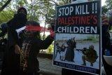 Massa yang tergabung dalam ormas Ahlulbait Indonesia (ABI) wilayah Bali membawa poster seruan saat aksi solidaritas dan penolakan agresi Israel terhadap Palestina di Denpasar, Bali, Senin (24/5/2021). Aksi tersebut untuk solidaritas kemanusiaan dari ABI Bali sekaligus memberikan edukasi kepada masyarakat tentang keadaan yang terjadi di Palestina. ANTARA FOTO/Nyoman Hendra Wibowo/nym.